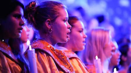 A choir of young women dressed in robes and holding candles