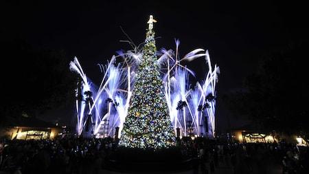 Un arbre décoré avec des lumières de Noël et couronné d'un ange près d'une foule de personnes, d'arbres et de feux d'artifice