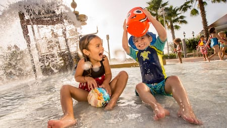 A young girl and her even younger brother splash about in a water play area at a Disney Resort hotel