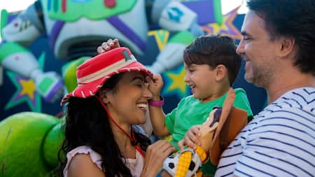 A woman in a cowgirl hat smiles with her family in front of a large figure of Buzz Lightyear