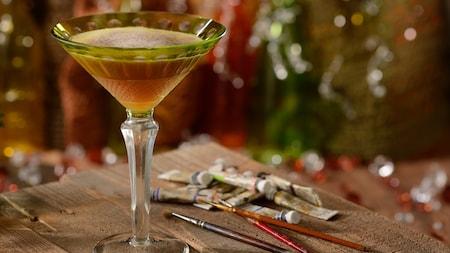 Un élégant verre à martini contenant un cocktail Night Monkey sur une table à côté de tubes de peinture à l'aquarelle et de pinceaux