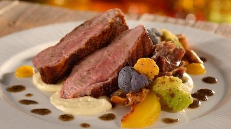 Un plato con rebanadas de pata de pato asada sobre puré junto con coliflor y una tajada de durazno cocida