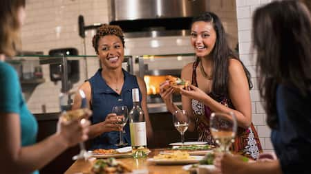 Two female friends enjoy artisanal pizza and wine