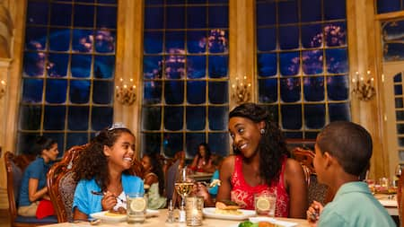 A mother and daughter and son enjoy dinner at Be Our Guest Restaurant in Fantasyland