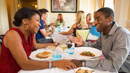 Una pareja charla en una mesa en un restaurante lleno