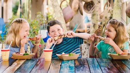 3 children eating chicken skewers