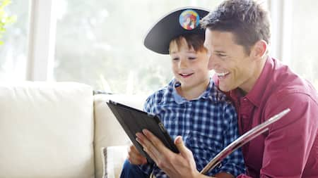 A man and a boy wearing a pirate hat look at a tablet together