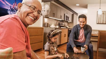 2 men smile and play Dominoes with a little girl wearing Mickey Ears