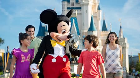 A family walks with Mickey Mouse near Cinderella Castle