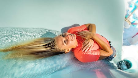 A young Guest crosses her arms, preparing for a steep drop down a water slide