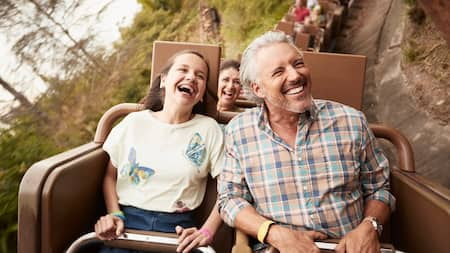 Un adulto y un joven Visitante pasean en Big Thunder Mountain Railroad