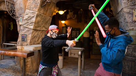 2 young men wearing face masks while dueling with lightsabers outside at Star Wars Galaxy's Edge
