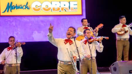A man with a trumpet sings into a microphone as a mariachi band plays in the background in front of a sign that reads, 'Mariachi Cobre'