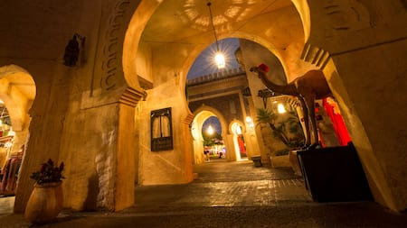 A camel statue beneath a hanging lantern in a passage at the Agrabah Bazaar at Epcot in Walt Disney World Resort at night