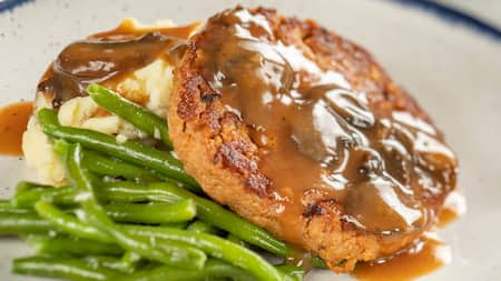 A slice of meatloaf, mashed potatoes with gravy and string beans on a plate