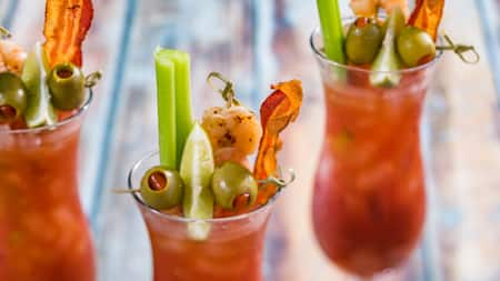 Three glasses of Bloody Marys garnished with bacon, celery, lime, olives, and shrimp