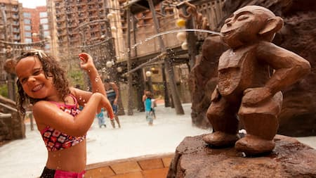 A little girl in the splash zone within the Aulani Resort pool area