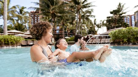 A family of 4 playing in a pool at Aulani Resort