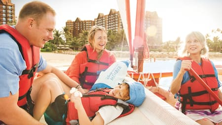 A family of 4 on a small boat in the lagoon at Aulani