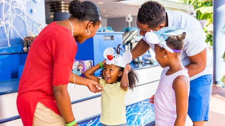 A mother, father and their 2 daughters smiling while outdoors at a theme park