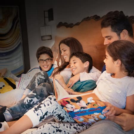 A family of 5 wearing cozy pajamas snuggles up in bed, reading bedtime stories