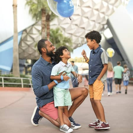 A man kneeling beside his 2 young sons beside Spaceship Earth at Epcot