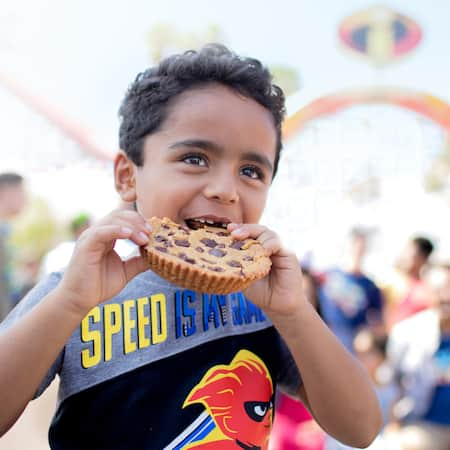 A boy takes a bite of a chocolate chip cookie in front of the Incredicoaster at Disneyland Resort
