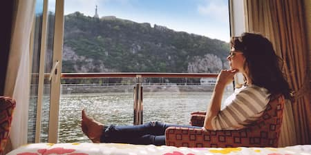A woman seated on a chair looks out her stateroom window at a mountainside village while cruising on a river