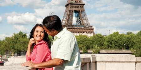A couple gazes into each other's eyes near the Eiffel Tower in Paris