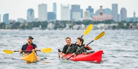 Three men paddle 2 kayaks in the water with the Boston skyline in the background