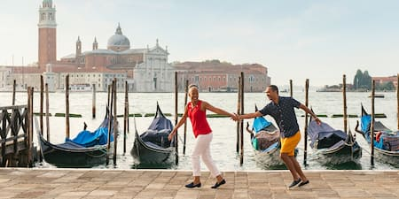 A couple holds hands as they stroll past docked gondola boats along the Venice Grand Canal