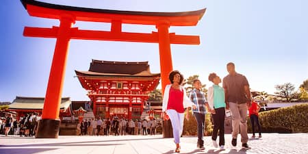 A family of four walks past a Tori gate near the entrance to a Japanese temple