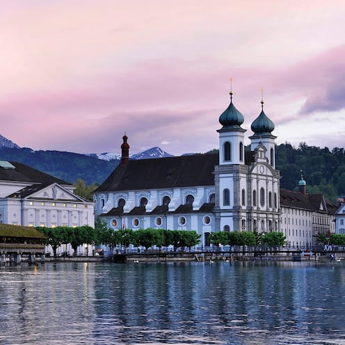 The Alps loom over a charming town on a lake with a roofed pier