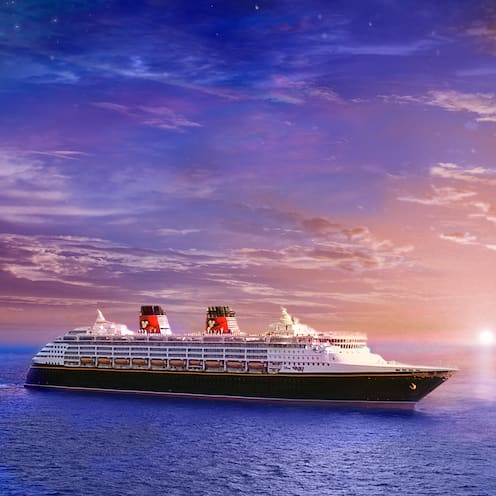 The Disney Magic cruise ship sail across the sea at sunset