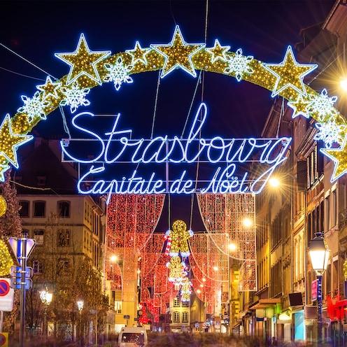 A lit-up sign between two buildings says Strasbourg Capitale de Noel
