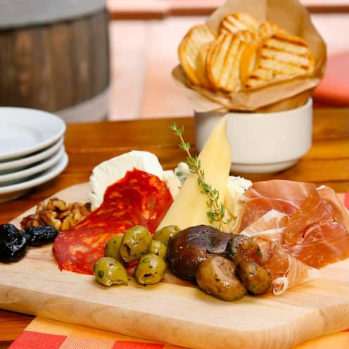 A charcuterie platter, with assorted meats, cheeses and olives, sits atop a wooden table alongside a glass of wine, bowl of bread and a stack of plates
