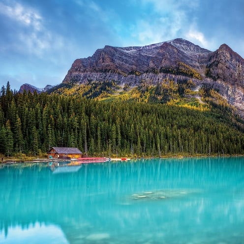 Pine trees line the banks along the calm waters of Lake Louise as it flows past a log cabin and through a mountain range