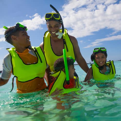 A family of 5, wearing snorkels, masks and vests, is all smiles as they stand in the clear ocean waters