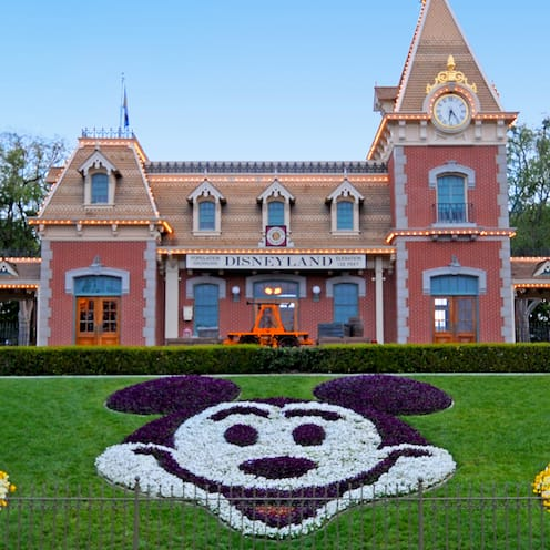 The Main Entrance to Disneyland Park with the train station and floral Mickey display