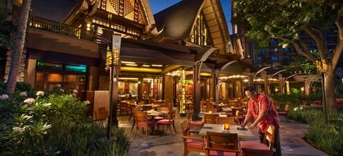 夜のアウラニ・リゾートのレストランで、屋外ダイニングエリアのテーブルをセットするスタッフ