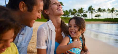 A family sitting on a sandy beach smile and laugh together