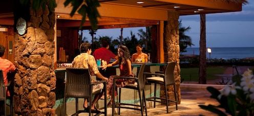 わらぶき屋根の屋外バーで、夜のカクテルとオーシャン・ビューを楽しむリゾートウェアの男女