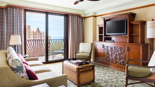 ソファ、オットマン、ランプ 2 個、椅子 2 脚、薄型テレビ、バルコニーのあるお部屋