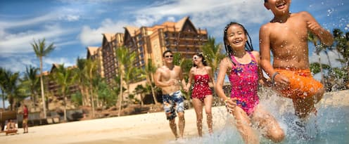 A family splashes in the water at Ko Olina Beach