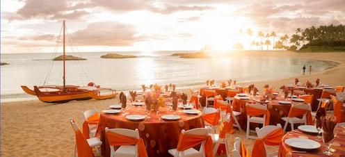 ビーチフロント沿いの砂浜の上に華やかにセッティングされたテーブルセット