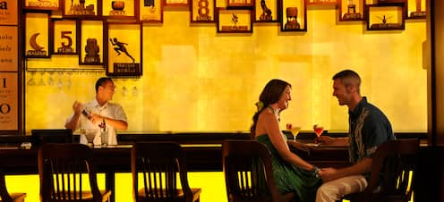 A couple shares a moment and tropical cocktails while a bartender mixes drinks with a martini shaker