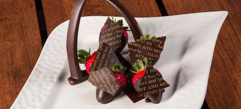 A plate of chocolate-dipped strawberries is presented with a chocolate version of the Aulani arch.