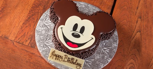 "A chocolate cake shaped and decorated like Mickey Mouse with an inscription reading ""Happy Birthday"""