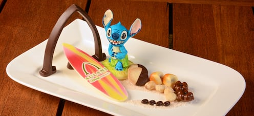 A plate of small treats is adorned with a chocolate arch, a replica surfboard and a Stich figurine.