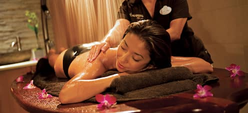 A masseuse performs therapeutic massage on a woman lying on a spa table, under jets of water